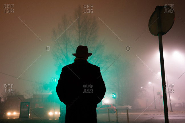 Man with his hands in his pockets on a foggy street at night