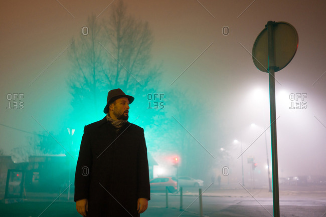Man walking on a foggy street at night