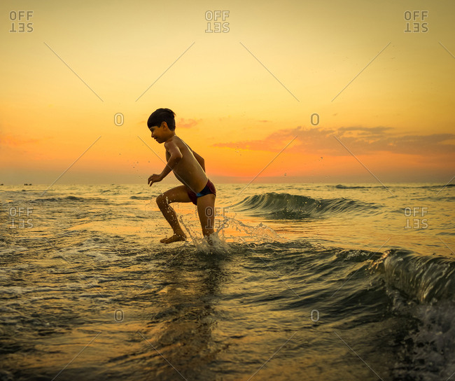 Boy running through waves in a colorful sunset