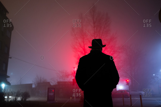 Man standing on a foggy street with his hands in his pockets at night