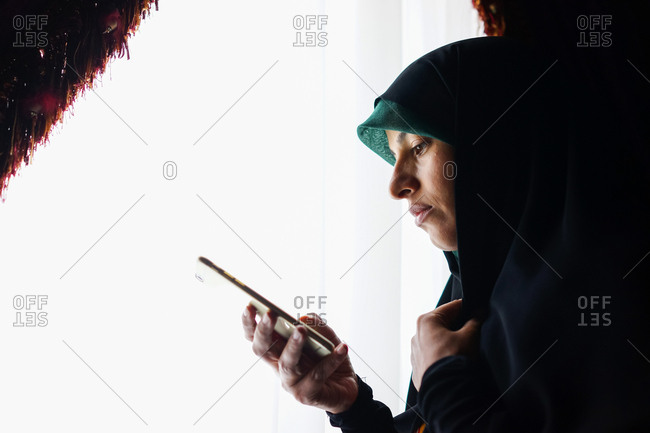 Muslim woman standing at a window checking her phone