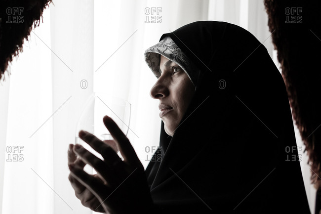 Muslim woman standing at a window holding a glass of water