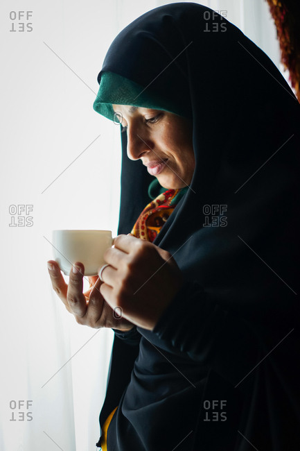 Muslim woman standing at a window holding a tea cup