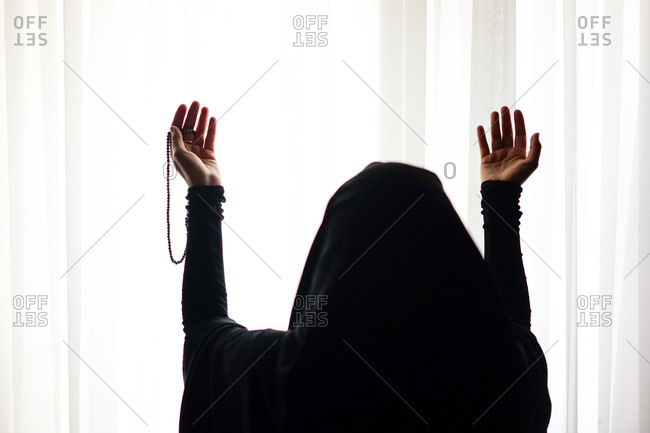Muslim woman standing at a window lifting her hands in prayer