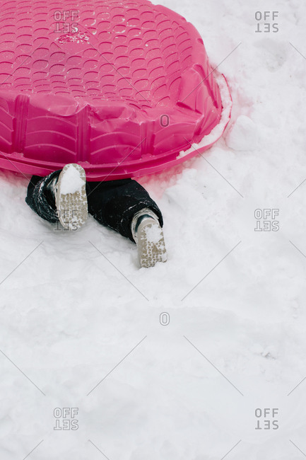 Legs of a child hiding under a pink kiddie pool in the snow