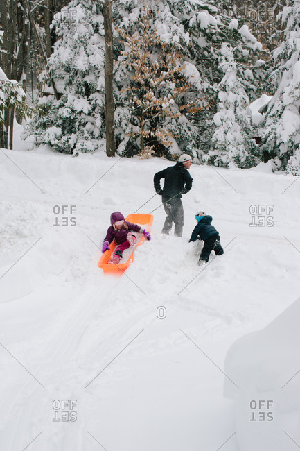 Father and two kids playing together in the snow