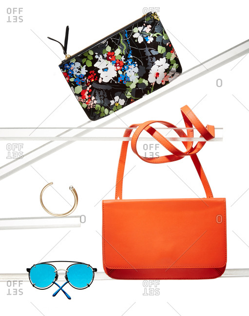 Handbags, bracelet and sunglasses on glass display tubes