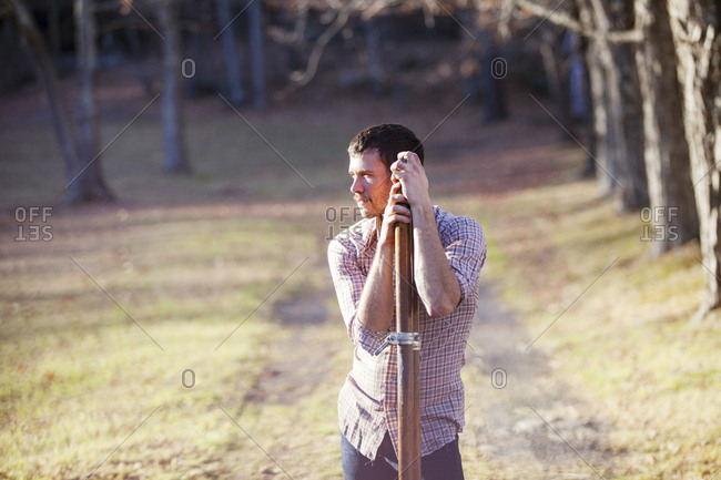 Man with oars looking away while standing on field in forest