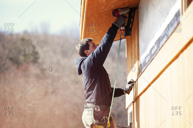 Worker using drill machine while constructing house during sunny day