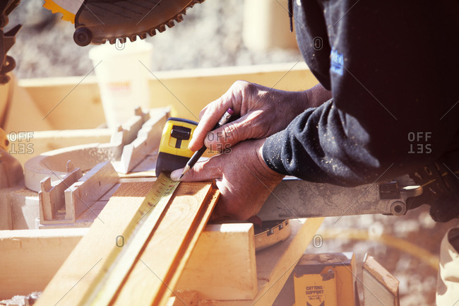 Midsection of worker measuring wooden planks at construction site