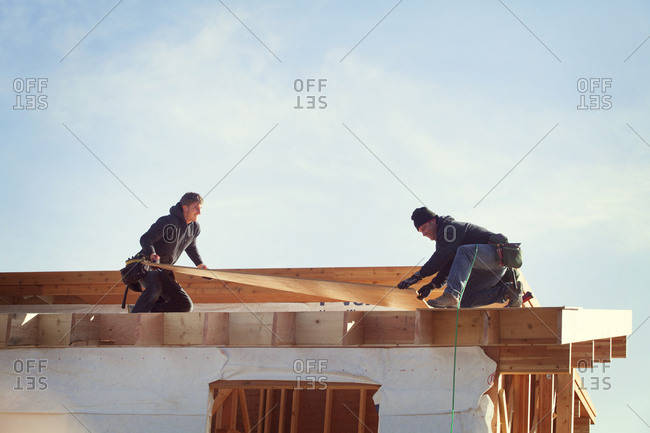 Workers constructing roof beam against sky during sunny day