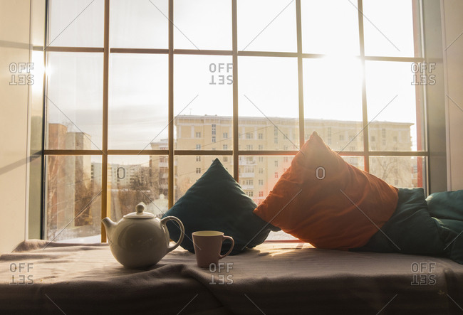 Kettle with cup by cushions on alcove window seat at home