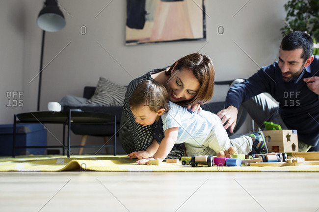 Parents and son playing with toy train at home