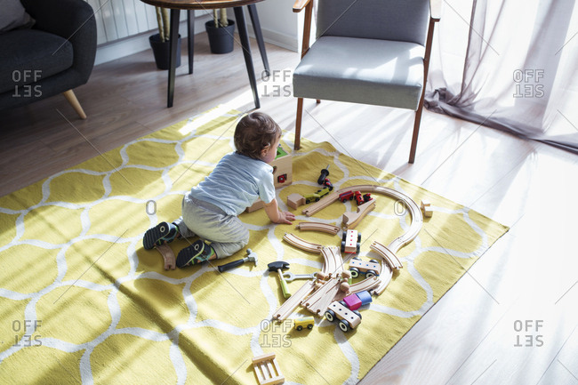 High angle view of baby boy playing with toy train at home