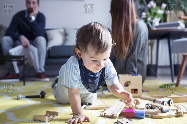 Boy playing with toy train while parents in background