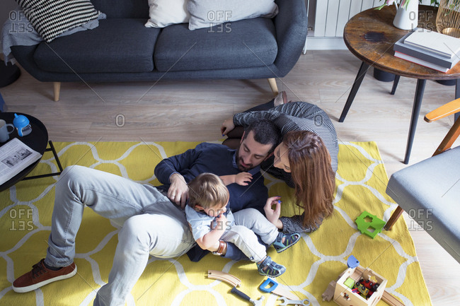 High angle view of cheerful parents playing with son at home