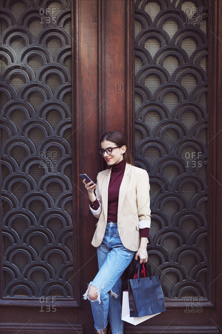 Woman with shopping bags using mobile phone while standing by closed door