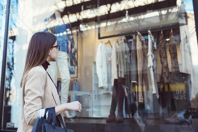 Side view of woman looking in shop window while shopping in city