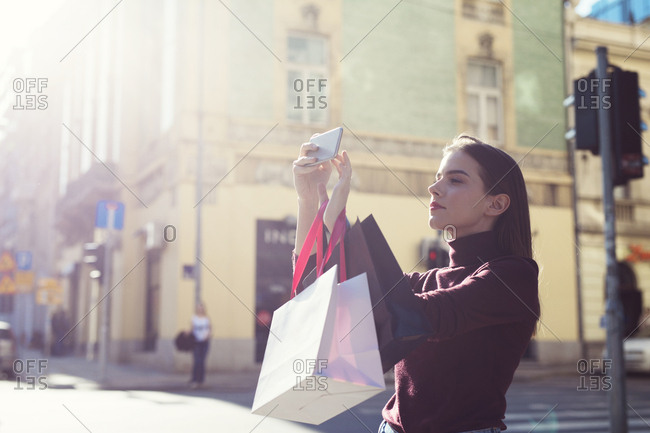 Woman with shopping bags photographing on city street during sunny day