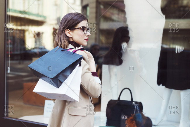 Woman with shopping bags looking in shop window