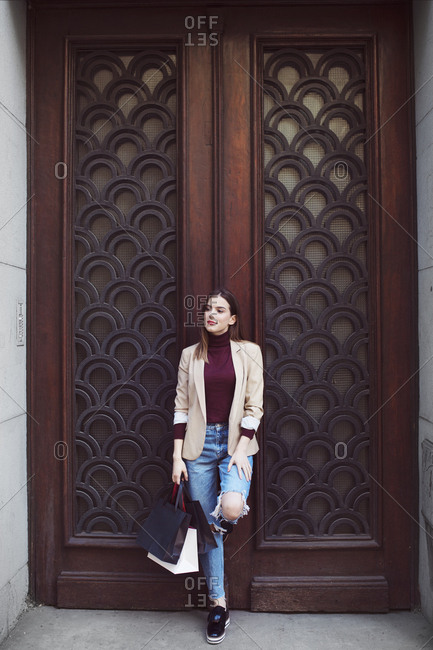 Woman with shopping bags looking away while standing by closed door