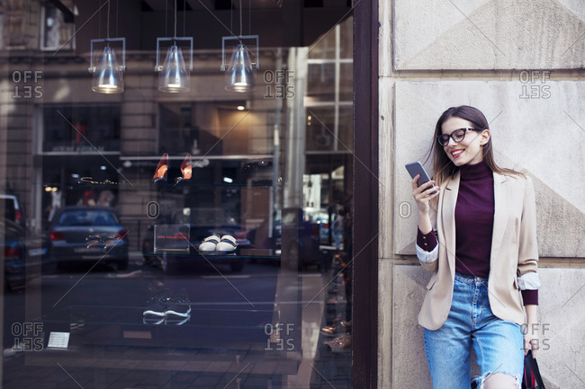 Woman with shopping bags using mobile phone while standing by wall in city