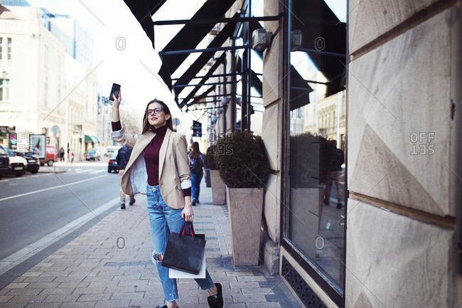 Woman with shopping bags and mobile phone standing on sidewalk in city