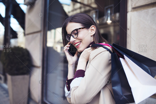 Happy woman with shopping bags talking on mobile phone by building