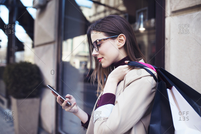 Woman with shopping bags using mobile phone while standing by building