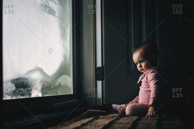 Baby girl sitting by condensed glass door at home
