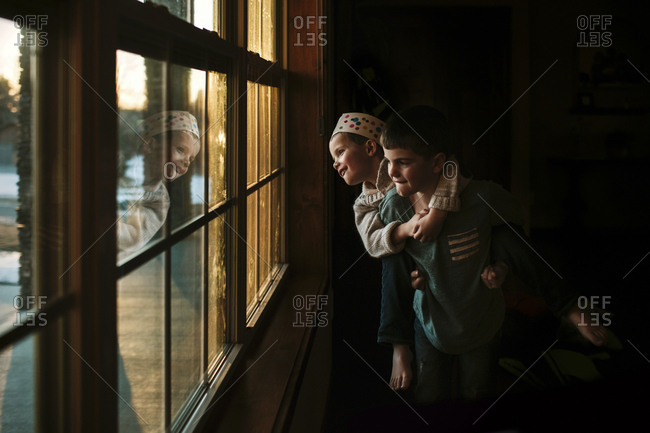 Playful boy piggybacking brother by window at home