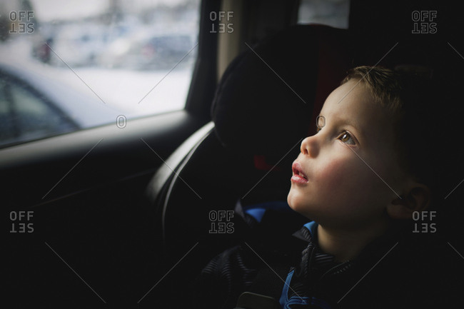 Thoughtful boy looking up while traveling in car