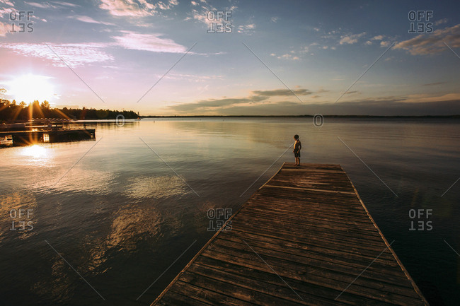 High angle view of shirtless boy standing on jetty against sky during sunset