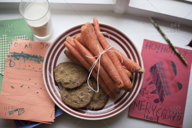 High angle view of carrots and cookies in plate with coffee by Christmas card on table