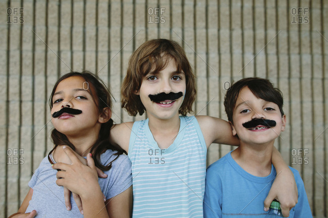 Portrait of happy siblings with artificial mustache against wall