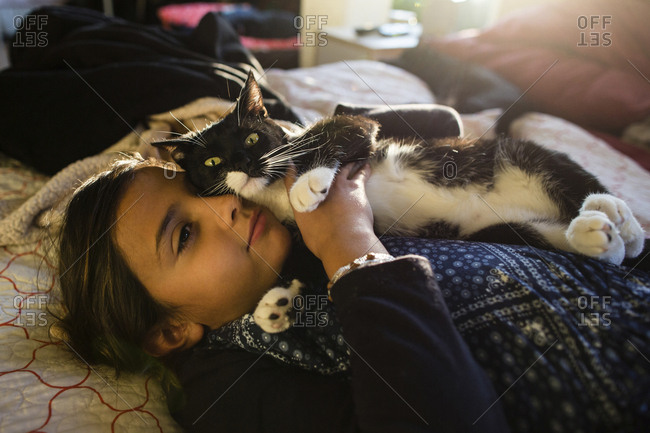 Girl with cat relaxing on bed at home