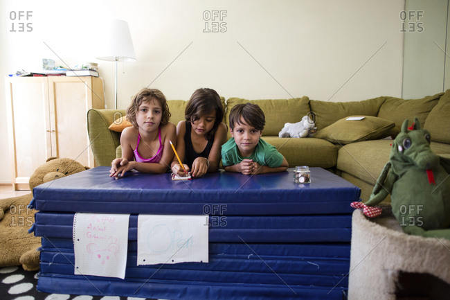 Portrait of siblings leaning on mattress stack at home