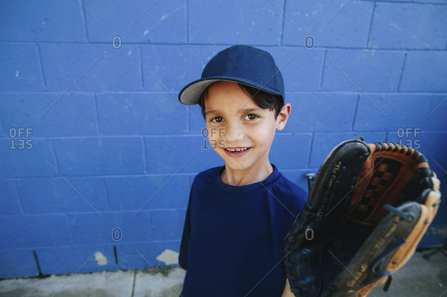 Portrait of happy boy wearing baseball glove standing against wall