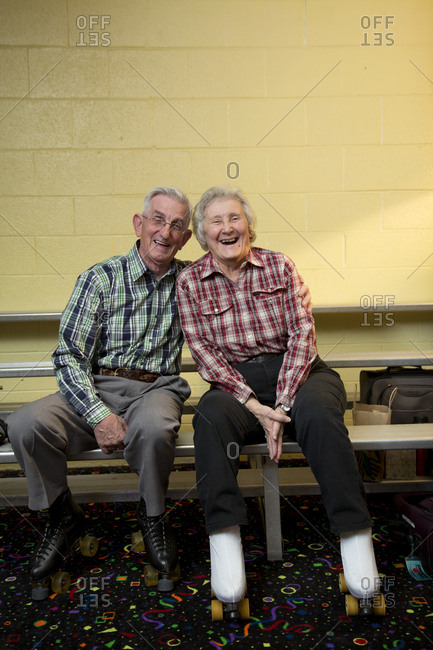 Portrait of happy senior couple sitting on bench at roller rink