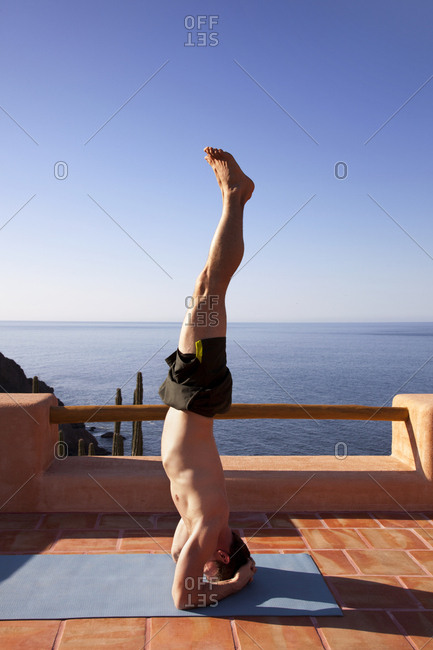Side view of man practicing handstand at resort against sea