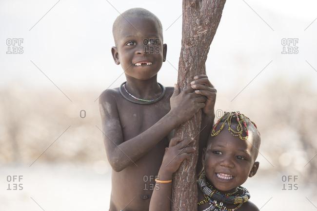 Happy siblings standing by tree