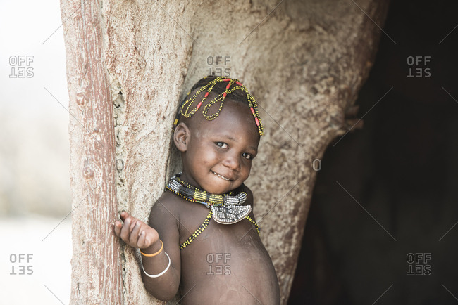 Close-up portrait of shirtless smiling girl leaning on wood