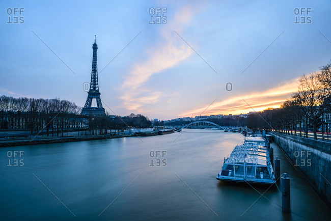 France, Paris - February 28, 2016: Eiffel Tower by river against sky at dusk