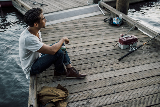 High angle view of thoughtful man holding drink can while sitting on pier over river