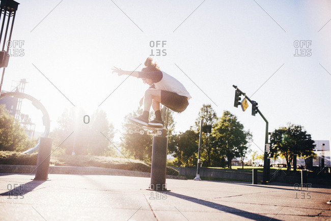 Man performing stunt with skateboard on city street against blue sky during sunny day