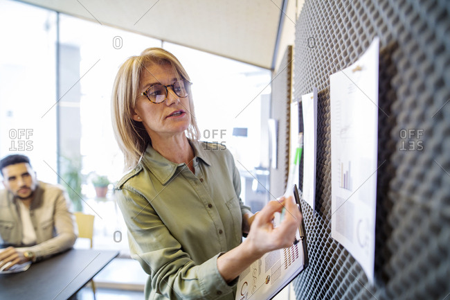 Businesswoman explaining documents to male colleague in meeting