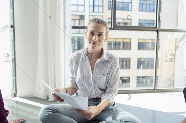 Portrait of businesswoman analyzing reports by window in office