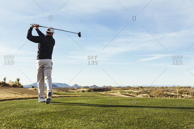 Rear view of golfer playing golf against on field against sky