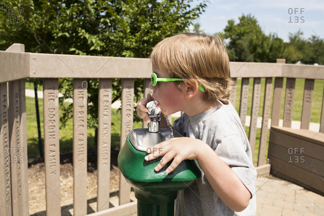 Boy drinking water from fountain at park