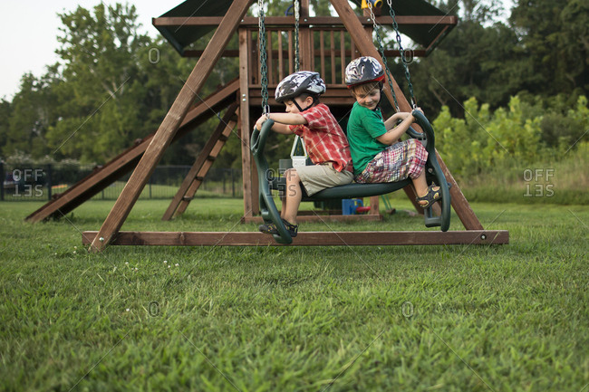 Playful brothers swinging in playground
